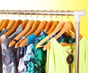 different clothes on wooden hangers on yellow background